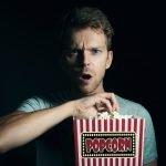 Man eating popcorn. movie trailers coming soon.